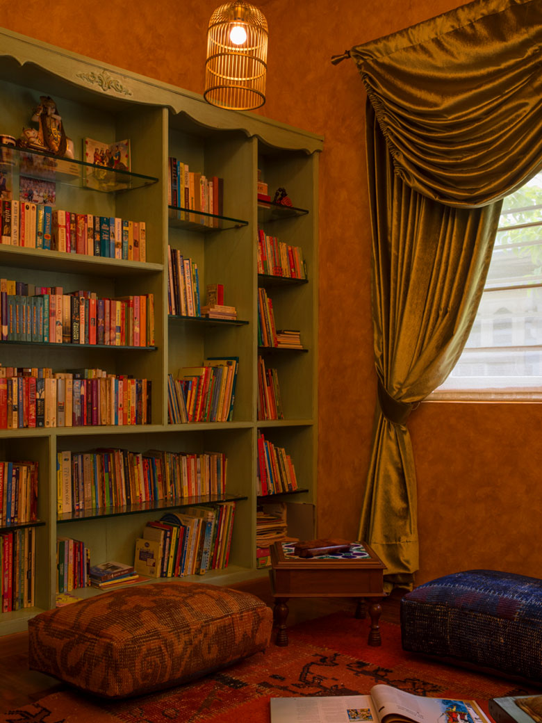 Bookshelf with green curtains