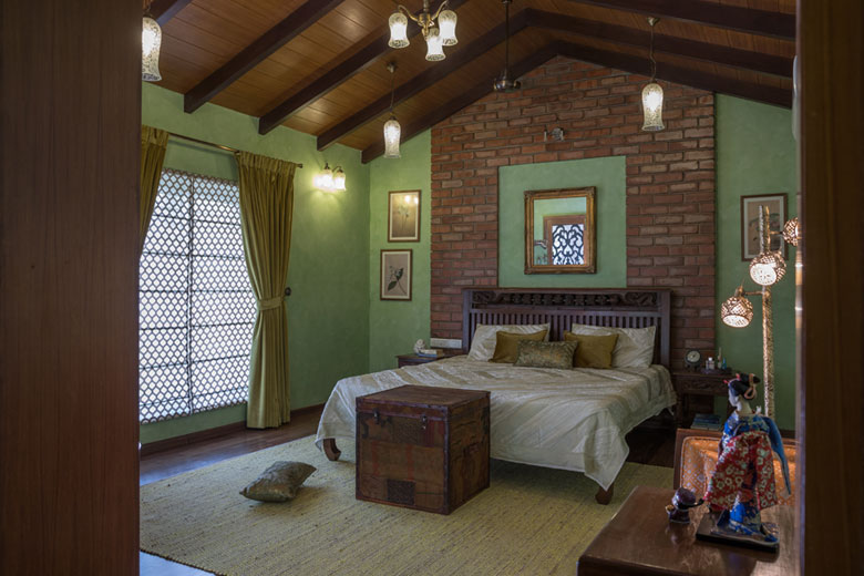 Green bedroom adorned with wood and bricks