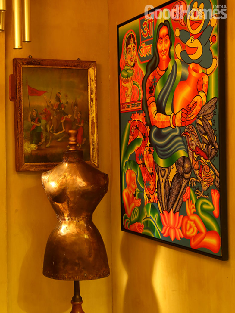 Metallic torso structure in a corner surrounded by paintings