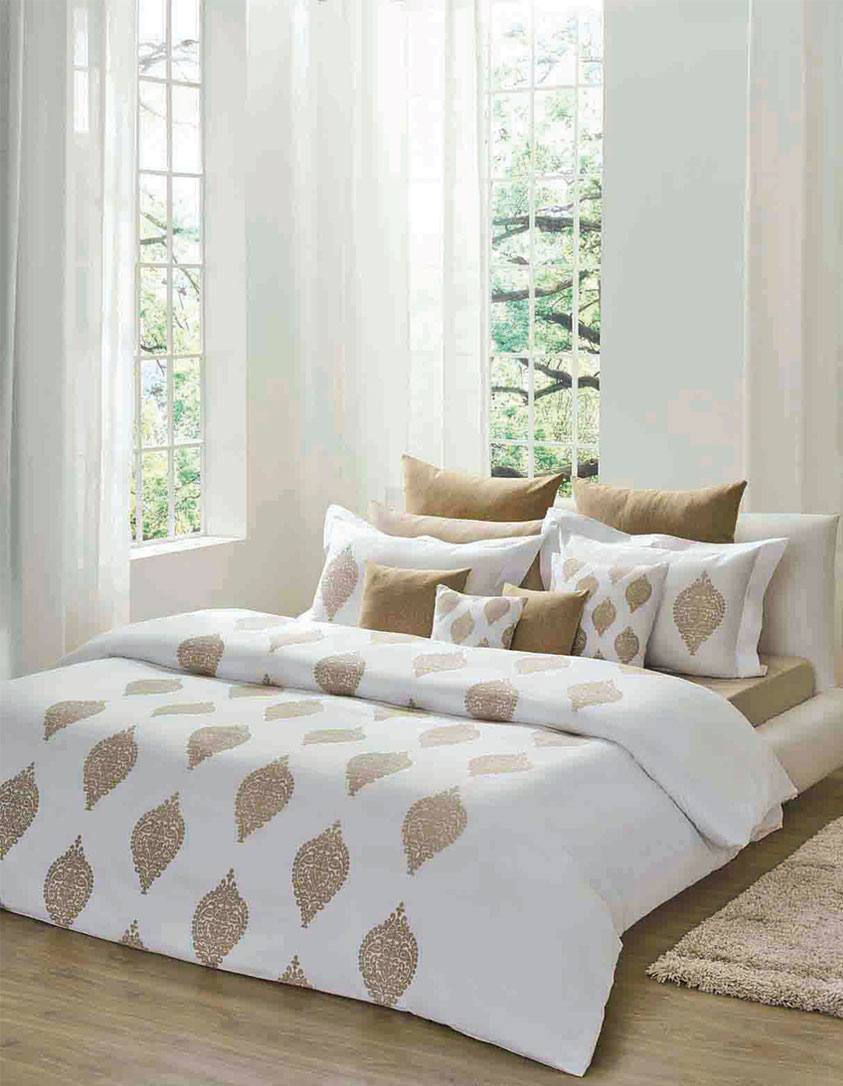 White bedroom with printed sheets and throw pillows