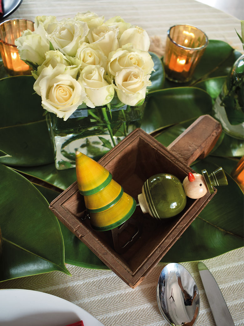 Table spread with white roses and banana leaves