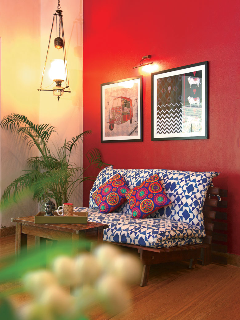 Red wall with fabric sofa in alibaug home