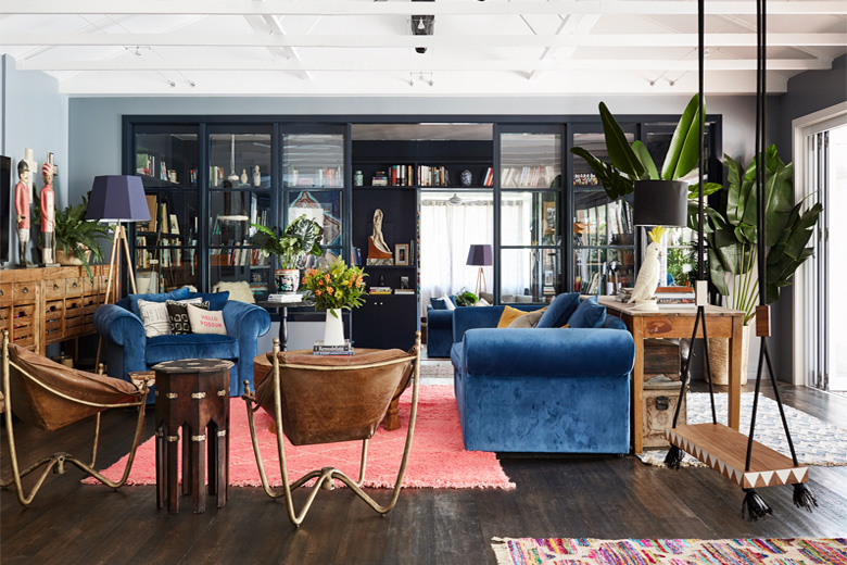 Living room with blue sofas and wooden floor.