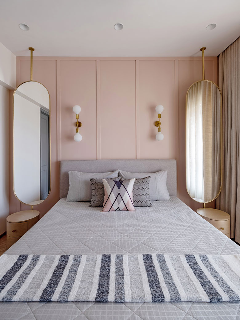 A minimal grey bed offsets the near salmon pink interiors of the room with brass pendant lights In the corner; Photography by Kuber Shah