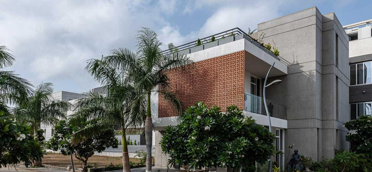 A striking terracotta facade defines this Surat home